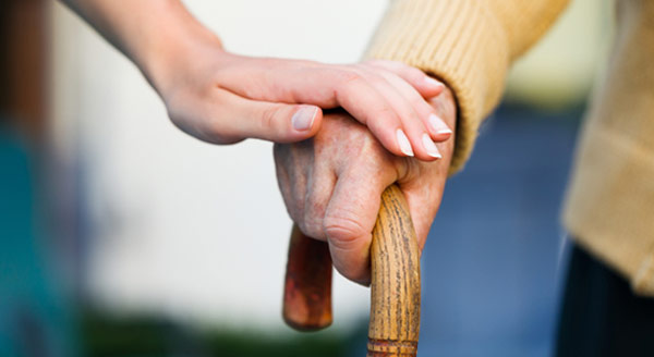 A caregiver comforts a man with a cane