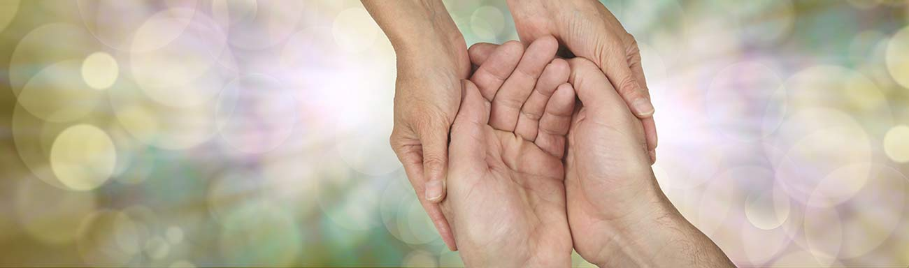 A caregiver embraces the hands of an individual with dementia